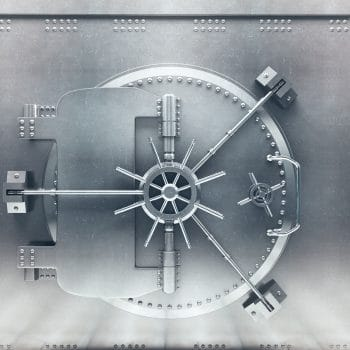 Front view of light silver bank vault door, closed